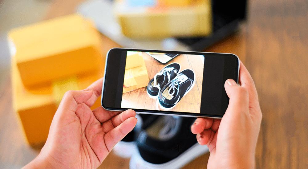 emprendedor tomándole foto a zapatillas desde su celular