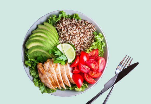plato de comida con pollo, palta, tomate sobre lechuga con tenedor y cuchillo