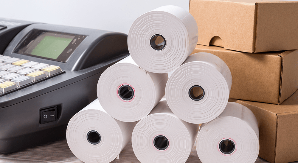 rollos de papel termico delante de POS y cajas de carton